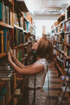woman searching library bookshelves